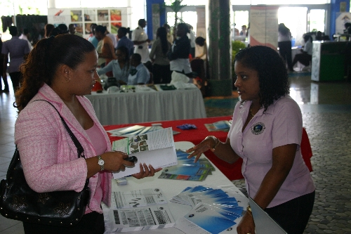 SBCS Customer Service Team Leader, Tricia Maharaj, explains SBCS programmes to visitor